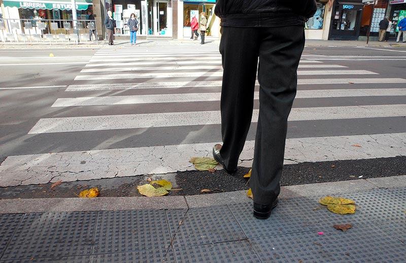 Un peatón se dispone a cruzar por un paso de peatones con los bordillos rebajados.