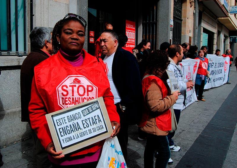 Queen Jona sujeta una pancarta a las puertas del Banco de Santander.