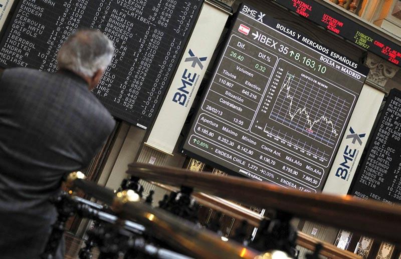 Un intermediario mira el panel del Ibex 35 en la Bolsa de Madrid.