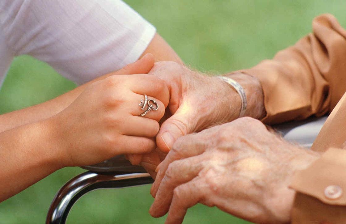 Una cuidadora le da la mano a un anciano.