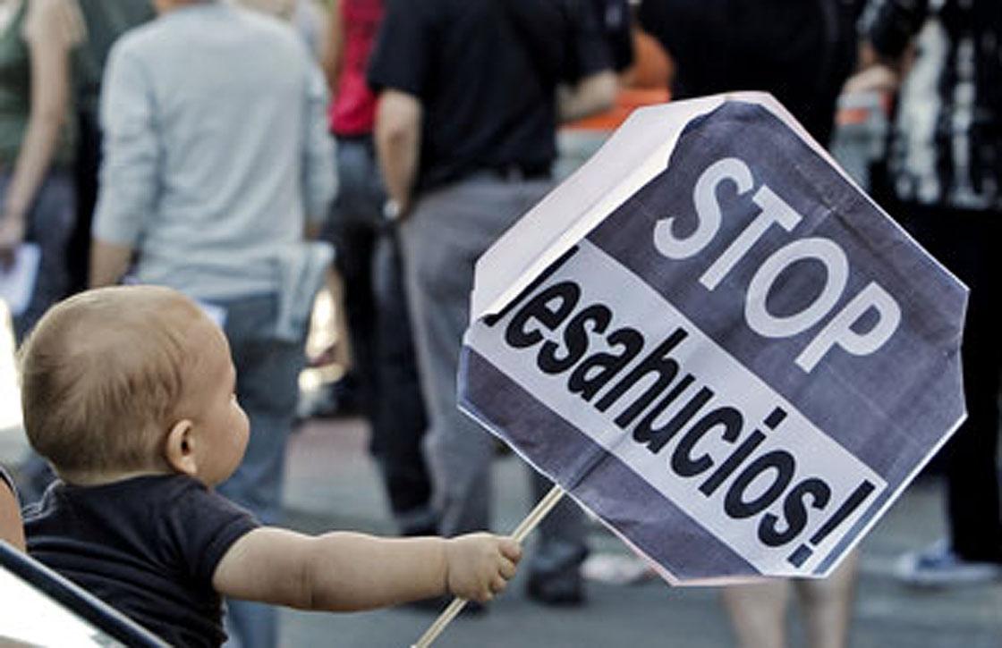 Un niño con un cartel de stop desahucios.