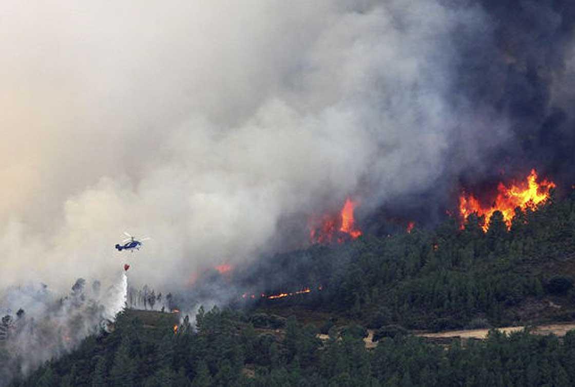 Un helicóptero descarga el agua sobre uno de los focos del incendio.