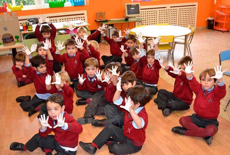 Varios alumnos con las manos pintadas de blanco.