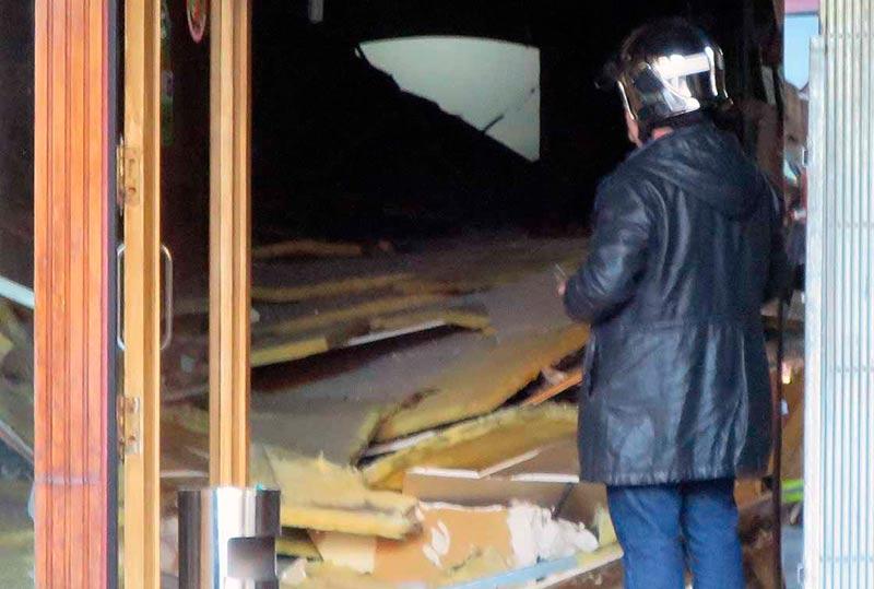 Un técnico observa los escombros en el interior del local.