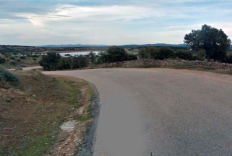 La carretera de Pelayos hasta la autovía, con la presa de Santa Teresa al fondo.