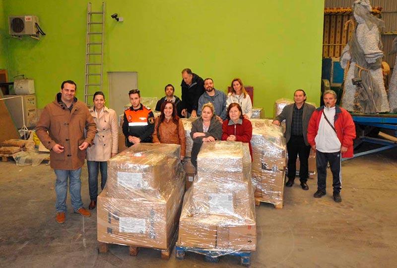 Alcalde y concejales junto a los palés del material donado.