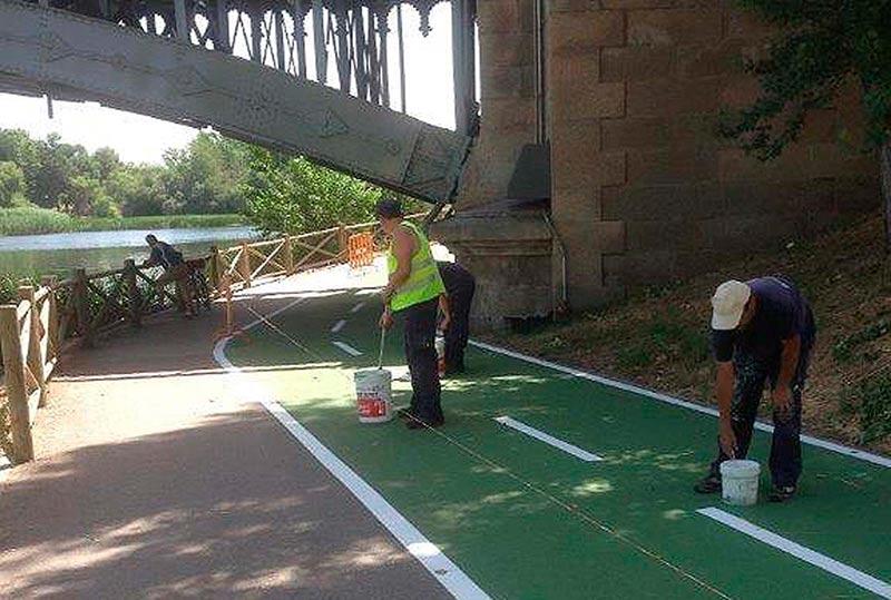 Dos trabajadores pintando bajo el puente Enrique Estevan.