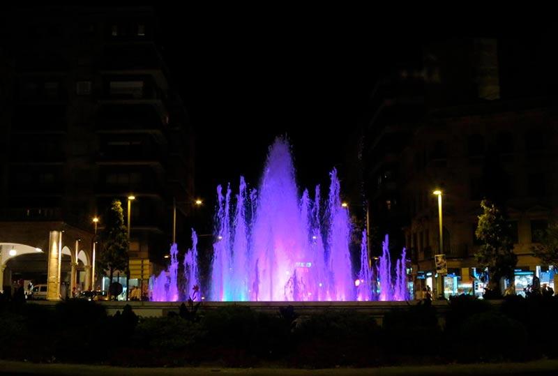 La fuente de la Puerta de Zamora iluminada de color púrpura.
