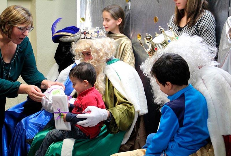 Dos niños reciben los regalos de los Reyes Magos.