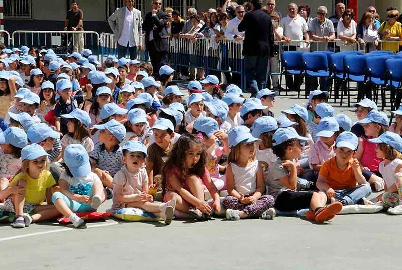 Niños al sol en un acto escolar.