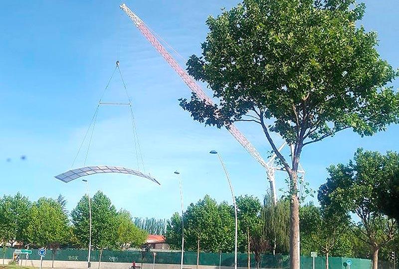 La grúa coloca parte de la nueva cubierta de la piscina climatizada de Garrido.