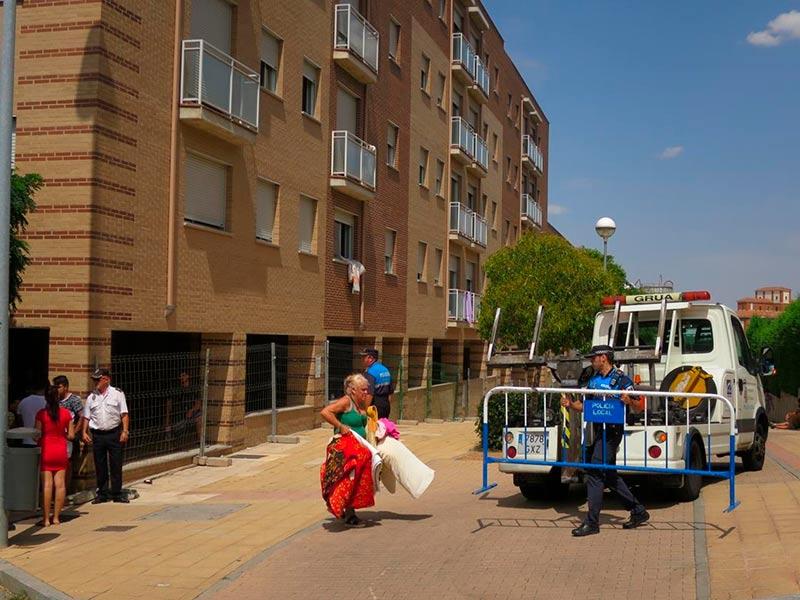 Una mujer saca algunos enseres del edificio ocupado.