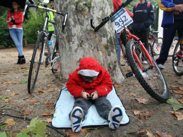 Miriam Chacón / ICAL Un niño se entretiene con el móvil a término de la Marcha ciclista Movistar