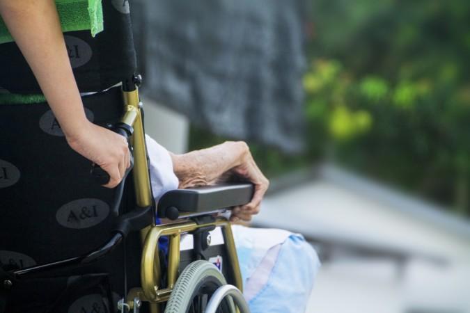 Una auxiliar de ayuda a domicilio llevando una silla de ruedas.