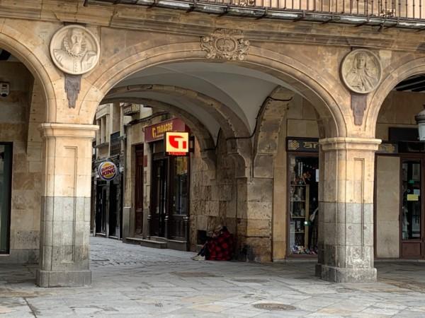 Una persona pidiendo en el arco de la calle Prior, en Salamanca.