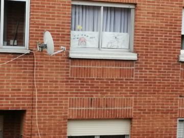 Los dibujos de unos niños expuestos en sus ventanas que se pueden ver desde la calle.