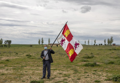 Eduardo Margareto / ICAL. El alcalde de Villalar, Luis Alonso, pasea por la campa vacía de Villalar con una bandera de Castilla y León