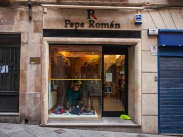 Pepe Román montando el escaparte de su tienda.