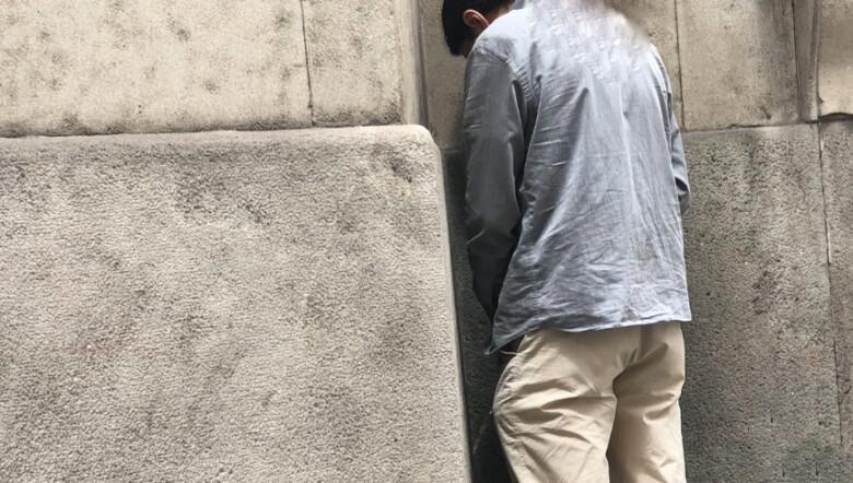 Un hombre orinando contra una pared.