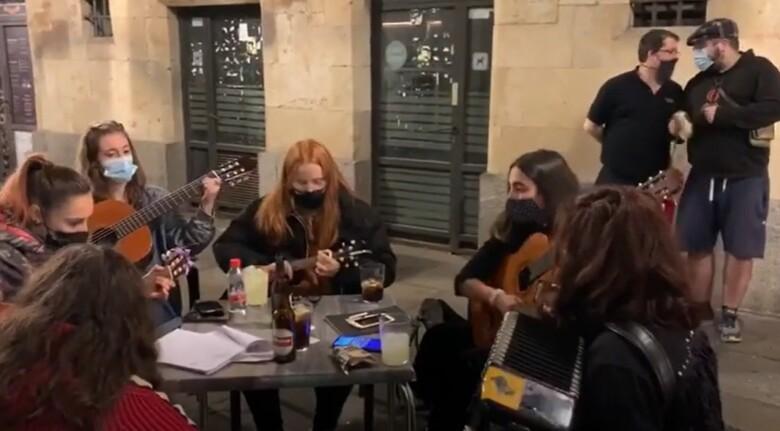 Un grupo de jóvenes toca en los soportales de la Plaza Mayor.