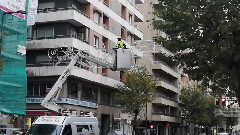 Los operarios montando las estructuras de la iluminación navideña en la calle María Auxiliadora.