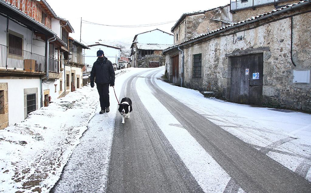 Vicente / ICAL. Un vecino pasea por una de las calles nevada de Candelario (Salamanca)
