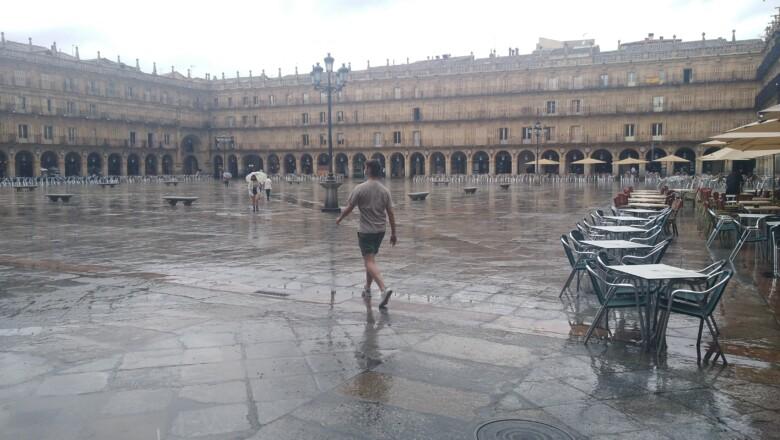 Un hombre pasea por la Plaza Mayor después del chaparrón.