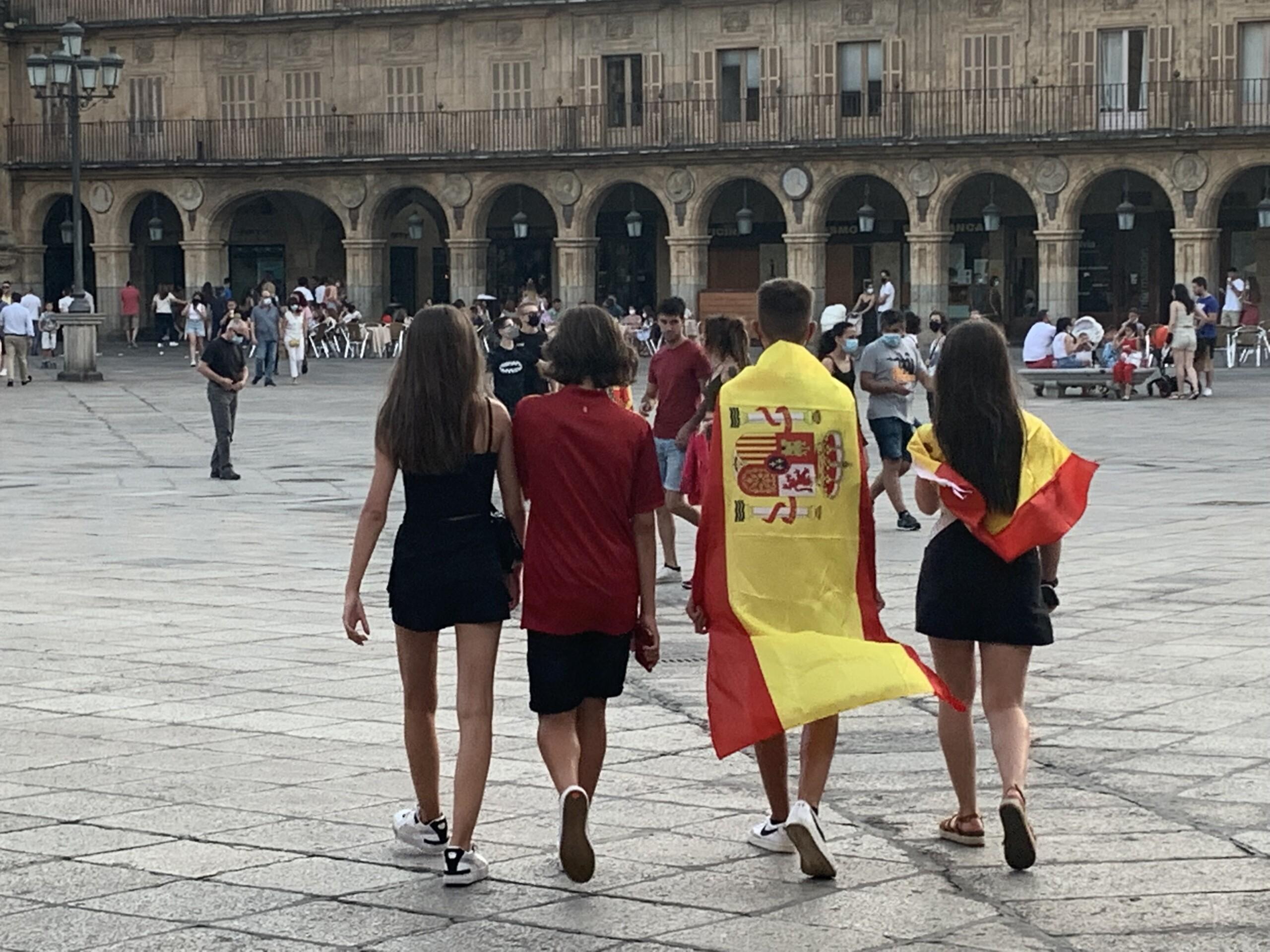 Jóvenes con banderas de España paseando por la Plaza Mayor de Salamanca.